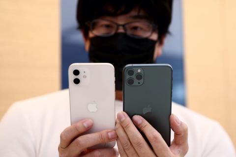 Un hombre sostiene dos modelos de iPhone 12