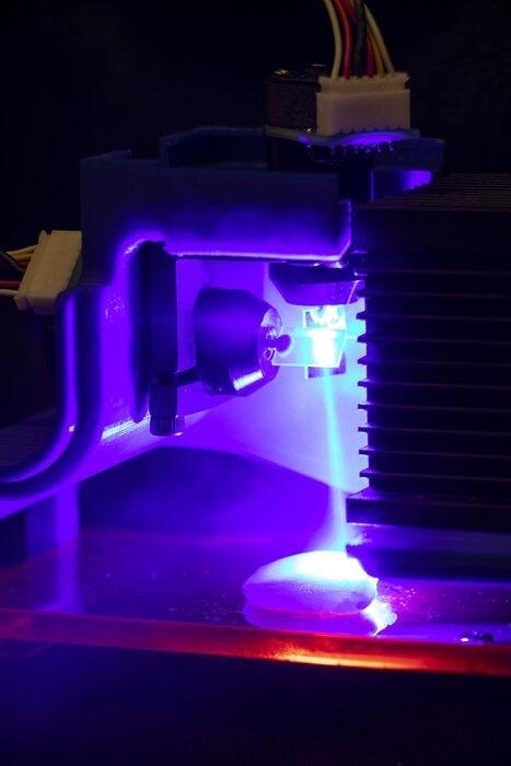 Pollo cocinado con láser azul. La luz se dirige por dos galvanómetros de espejos controlados por software.