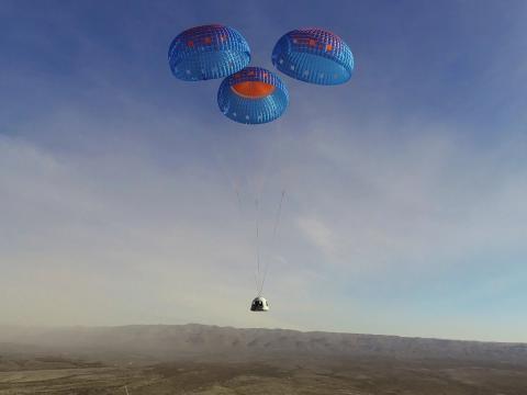 La cápsula de la tripulación de New Shepard se lanza en paracaídas a un aterrizaje en el sitio de lanzamiento uno de Blue Origin en Texas, el 14 de enero de 2021.