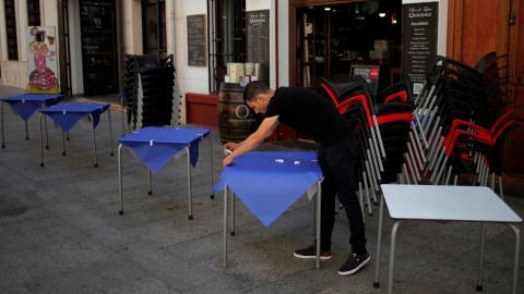 Un camarero prepara las mesas de una terraza en un restaurante de Ronda (Málaga)