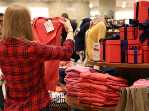 Una persona mira prendas de ropa de oferta en una gran superficie