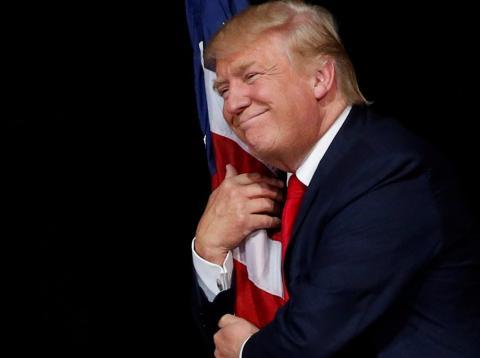 Donald Trump abraza una bandera de Estados Unidos
