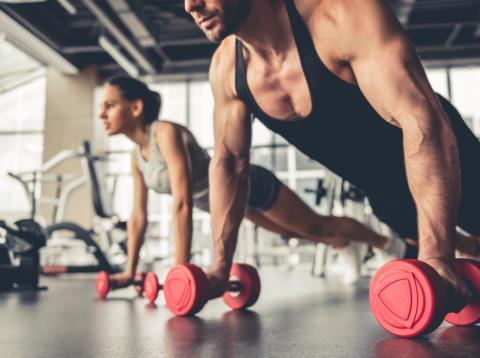 Personas hacen flexiones apoyados sobre pesas en el gimnasio