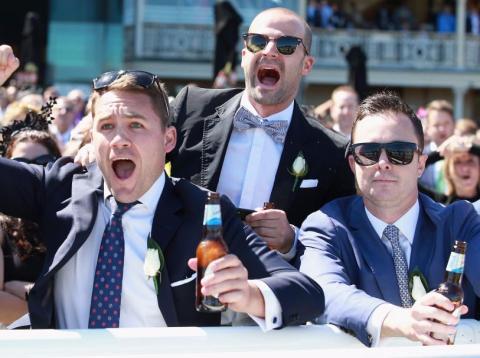 Tres hombres están emocionados entre la multitud con una cerveza en la mano celebrando una ocasión especial