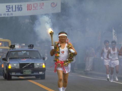 Un corredor porta la antorcha olímpica durante los Juegos Olímpicos de Corea del Sur en 1988