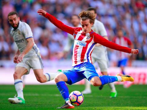 El jugador de fútbol Antoine Griezmann, del Atlético de Madrid, realiza un disparo contra el Real Madrid.