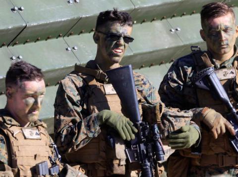 Tres marines estadounidenses descansan durante unas maniobras con la OTAN