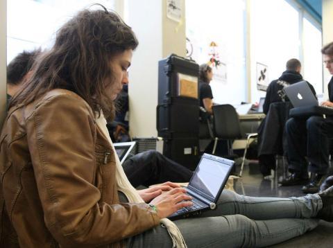Una persona consulta su ordenador sentada en una estación de transporte