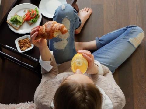 Una mujer desayunando croissant y zumo de naranja
