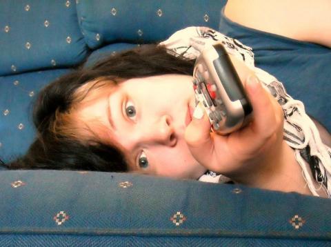 Una niña mira la tele desde el sofá con cara de aburrimiento.