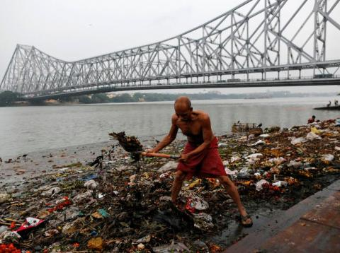 Un hombre limpia una de las orillas del Ganges.