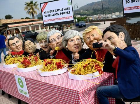 Varios manifestantes se ponen máscaras de los líderes del G7 durante una protesta en Italia.