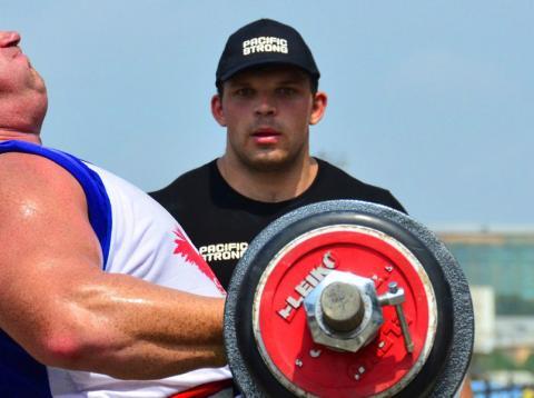 Un hombre levanta pesas en presencia de su entrenador