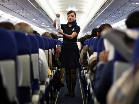 Azafata de avion lleno de pasajeros en pleno vuelo