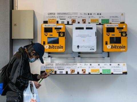 Una persona pasa por delante de unos cajeros de bitcoin