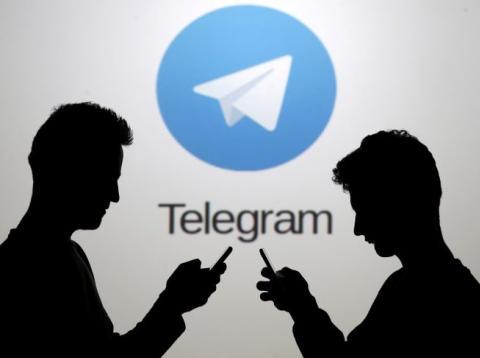 En esta ilustración, dos hombres posan junto a sus 'smartphone' frente a una pantalla que muestra el logotipo de Telegram.