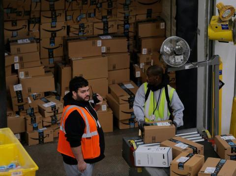 Dos operarios etiquetan y ordenan paquetes de Amazon.