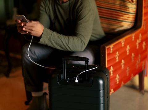 Un viajero consulta el móvil junto a su maleta.