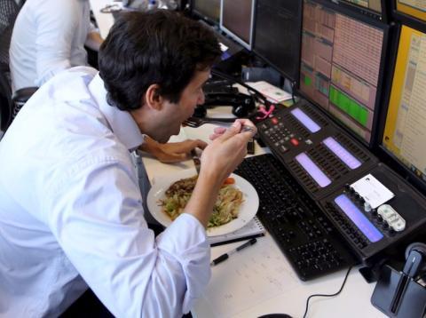 Un hombre comiendo delante de su ordenador