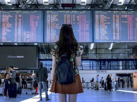 Joven en el aeropuerto buscando vuelos
