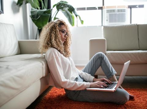 Una mujer con un ordenador en su salón.