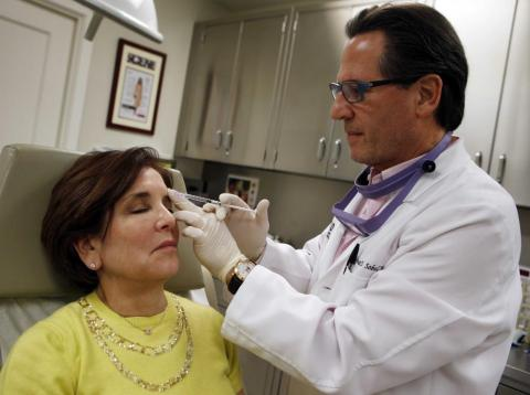 Howard Sobel, attending dermatologist and dermatologic surgeon at Lenox Hill Hospital in New York, demonstrates how Botox or other anti-wrinkle medicines are applied via syringe to a patient at his office in New York City March 22