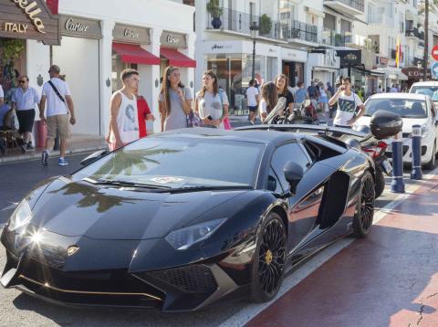 Una calle de Marbella con un deportivo aparcado.