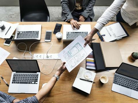 Personas con ordenadores y papeles.
