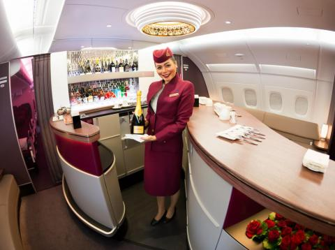 A flight attendant greets you upon entering Qatar Airways.