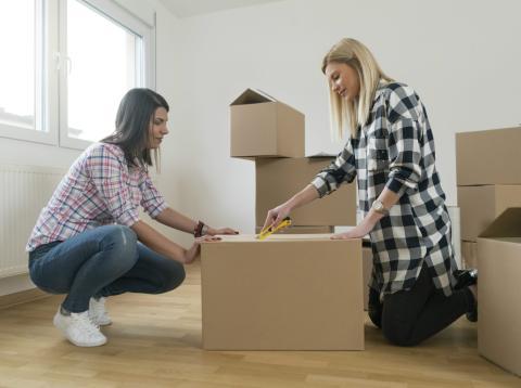 Unas jóvenes abriendo cajas de su mudanza a una nueva casa.