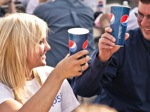 Dos personas brindan con un vaso de Pepsi.