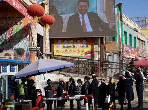 In this Nov. 3, 2017, photo, residents walk through a security checkpoint into the Hotan Bazaar where a screen shows Chinese President Xi Jinping in Hotan in western China's Xinjiang region.