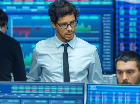 Traders mirando la bolsa, las letras del Tesoro y la evolución de los mercados.