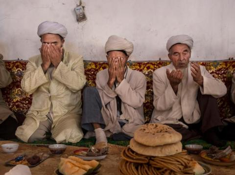 Uighur men pray before a meal during the Corban Festival, also known as Eid al-Adha, in Turpan, Xinjiang, in September 2016.