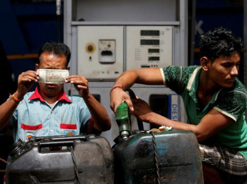 Trabajadores en India observan una rupia