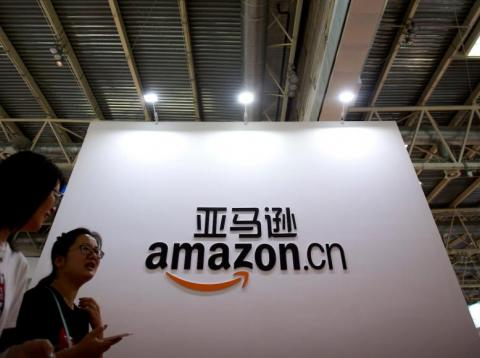 Visitors walk past a logo for Amazon China at the Beijing International Book Fair in Beijing on Aug. 23, 2017.