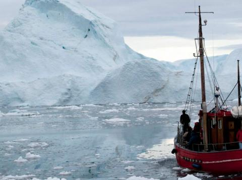 A boat steers slowly through floating ice, and around icebergs, all shed from the Greenland ice sheet, outside Ilulissat, Greenland.