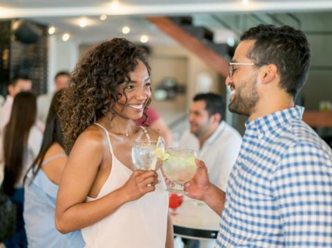 Dos personas conversan con una copa de ginebra