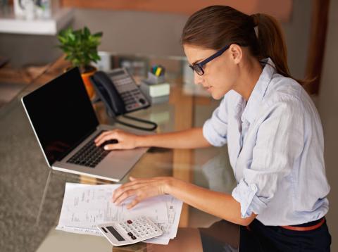 Una mujer delante del ordenador calculando cómo ahorrar.
