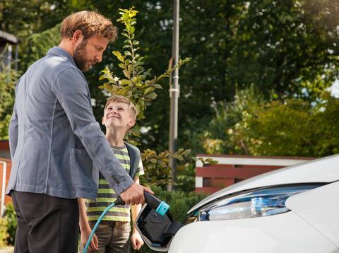 Un hombre cargando un coche eléctrico.