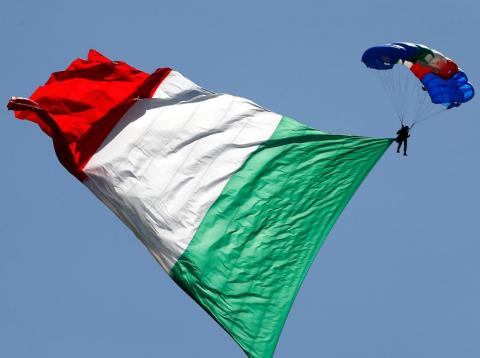 An Italian Army parachutist hoisting the Italian flag during the Republic Day military parade in Rome.