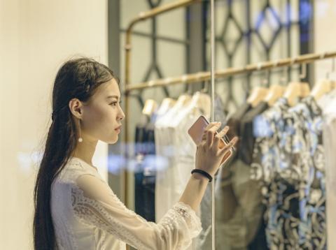 Una mujer observa el escaparate de una tienda de moda en Pekín