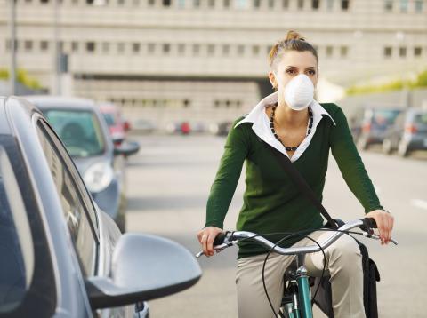 Una mujer utiliza una máscara respiratoria mientras transita en bicicleta.