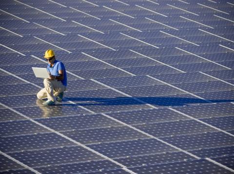 Un operario trabaja sobre paneles solares en una instalación fotovoltaica de energía solar renovable