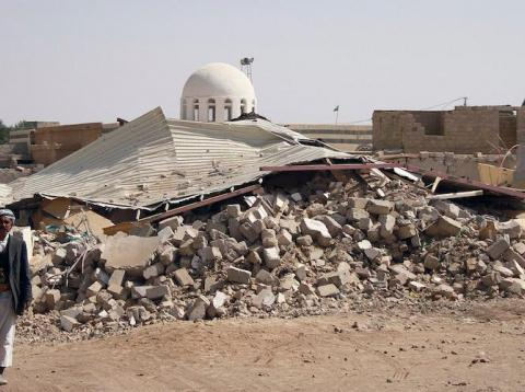 People walk past debris in Arhab, Yemen in January 2013 after a Houthi bomb was dropped there during a fight against Sunni tribesmen.