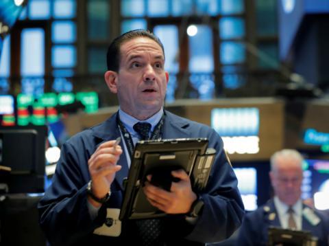 Trader sorprendido mirando a las pantallas en Wall Street