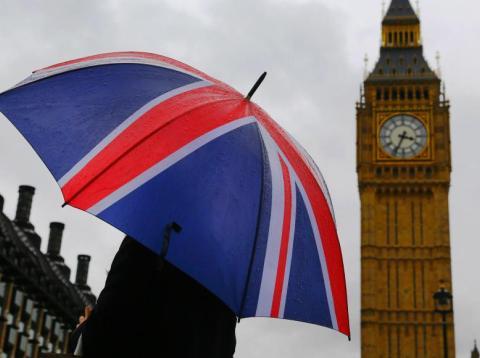 Una mujer lleva un paraguas con la bandera de Reino Unido frente a la torre del Big Ben en Londres, el 4 de octubre de 2014.