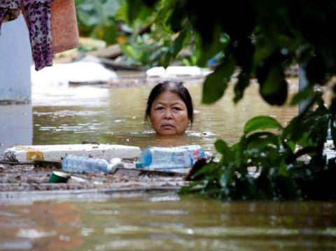 A woman wades through a submerged street at the UNESCO heritage ancient town of Hoi An after typhoon Damrey hit Vietnam in 2017.