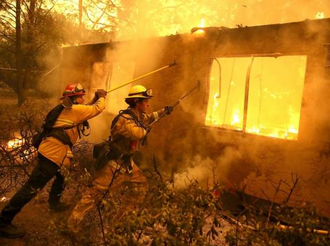 Firefighters try to keep flames from a burning home from spreading to a neighboring apartment complex as they battle the Camp Fire on November 9, 2018 in Paradise, California.