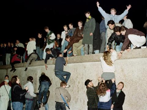 East Germans celebrate as they climbed the Berlin Wall at the Brandenburg Gate November 10, 1989.